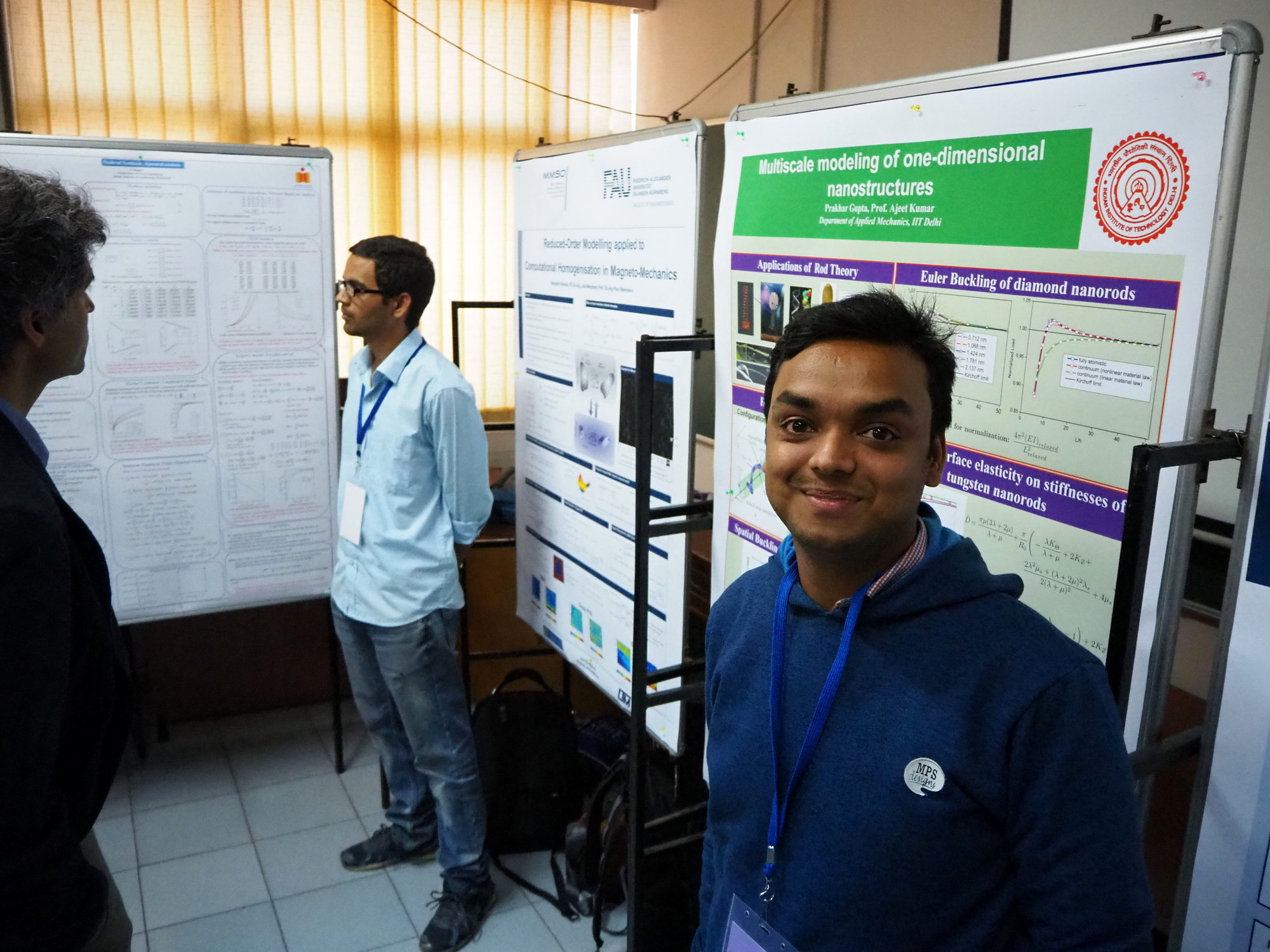 """Dr. Prakhar Gupta standing in front of his poster about """"Multiscale modeling of one-dimensional nanostructures""""."""
