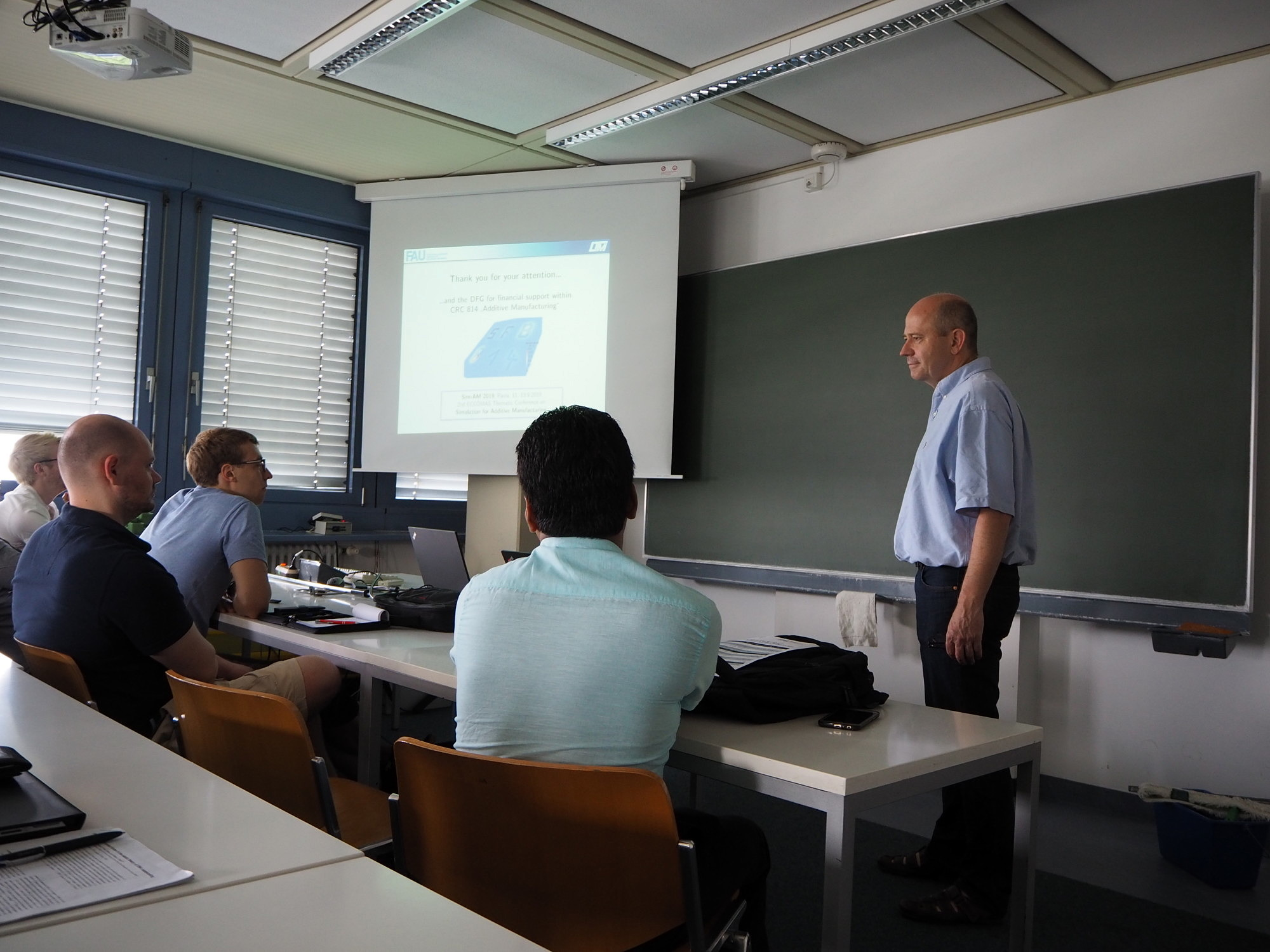 "Prof. Dr. Steinmann giving a presentation on ""Computational SBM-based Additive Manufacturing"" at Friedrich-Alexander-Universität Erlangen-Nürnberg."