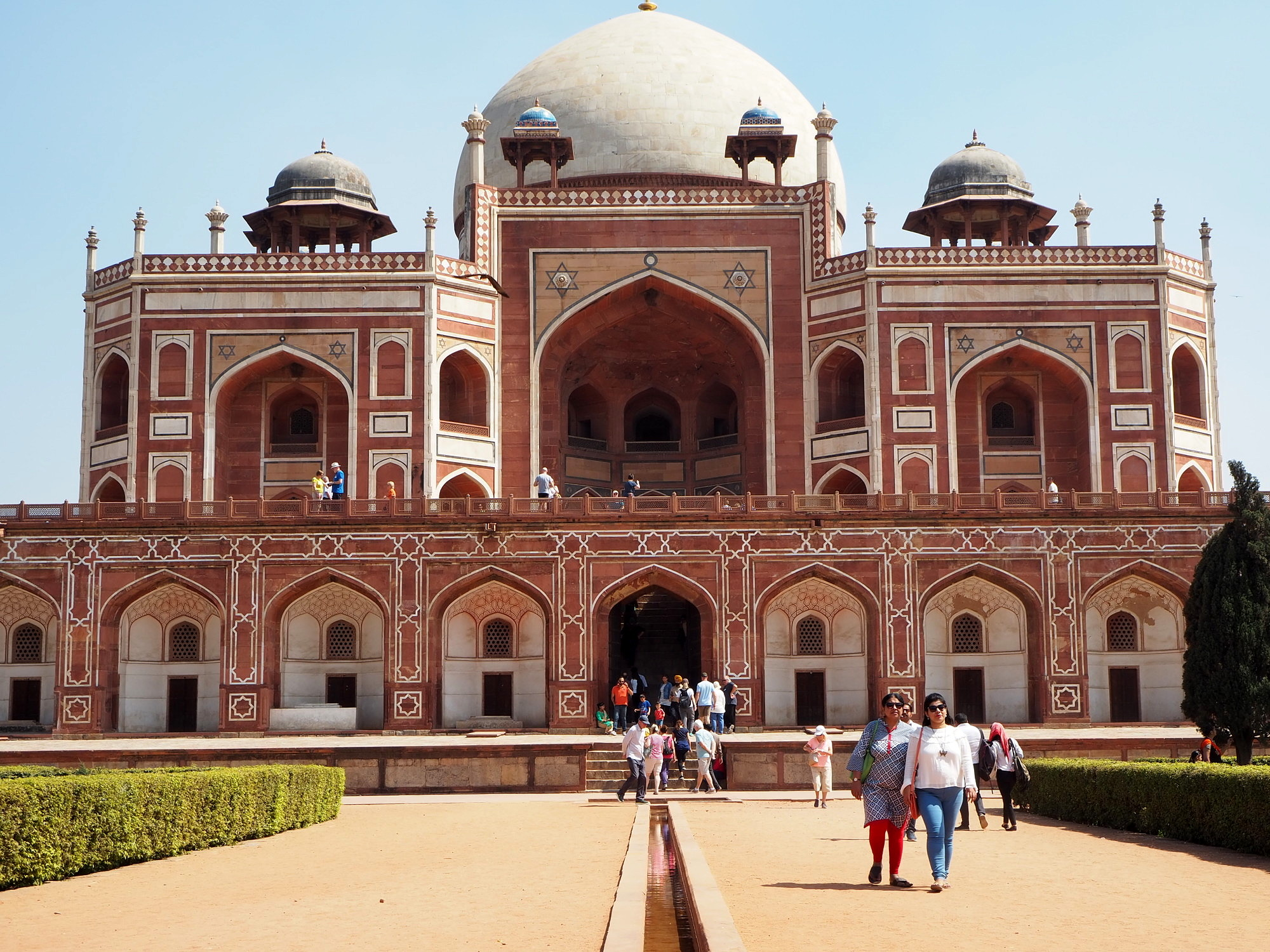 At Humayun's Tomb: A brownish-red building with a white pattern and several domes in different sizes on the roof. Some visitors are on and around the building.