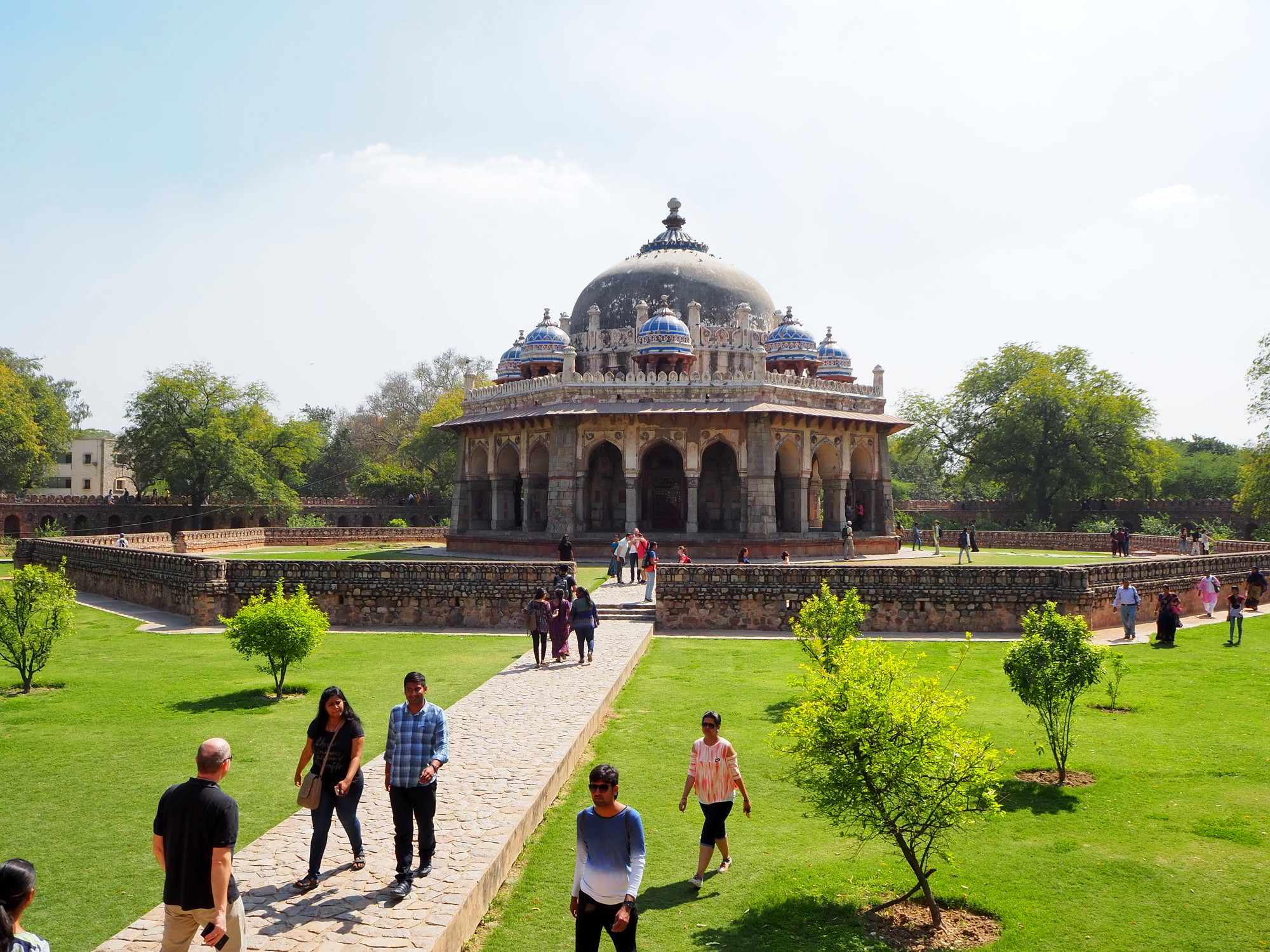 At Humayun's Tomb: A building made out of gray stone with several small blue domes around a large dome on the roof, surrounded by lime-green grass, tourists, and trees in the background.