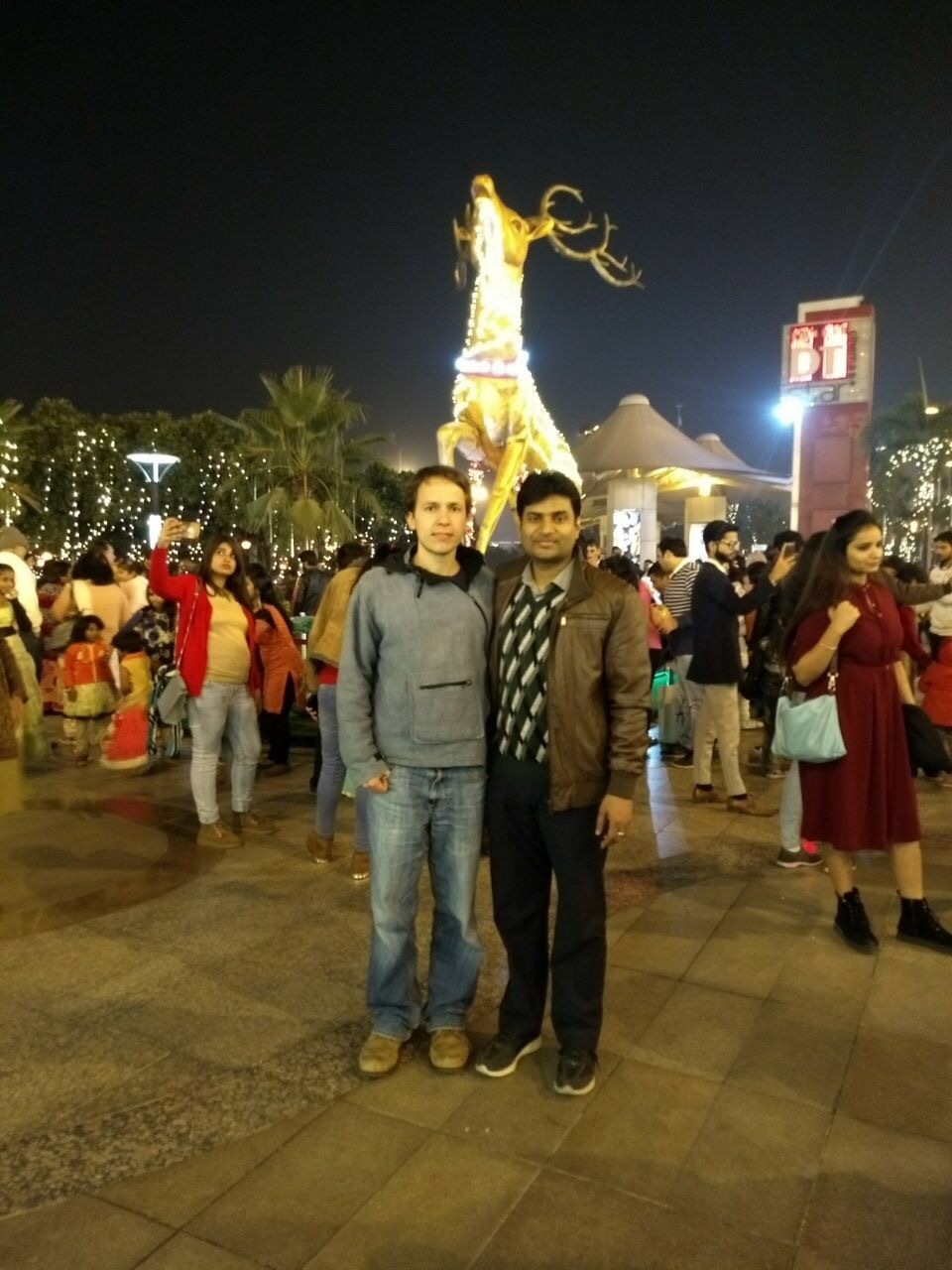 Markus Lohmayer and Prof. Dr. Ajeet Kumar posing for a photo at an open-air event at night in front of a large illuminated deer statue.